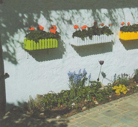 Клумба с борд.ром из серой вакки, минеральным защитным слоем и навесными контейнерами для цветов